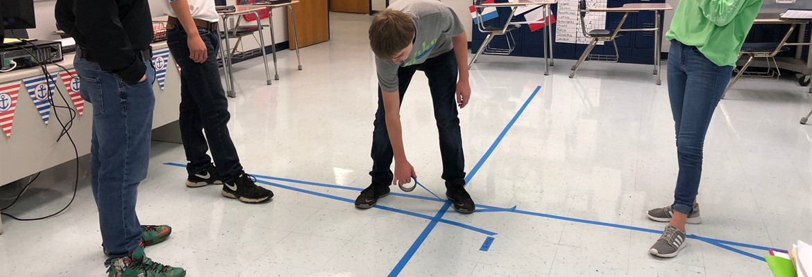 High School Math students worked on their skills of plotting points and  graphing lines in slope-intercept form by graphing on a classroom sized coordinate plane.